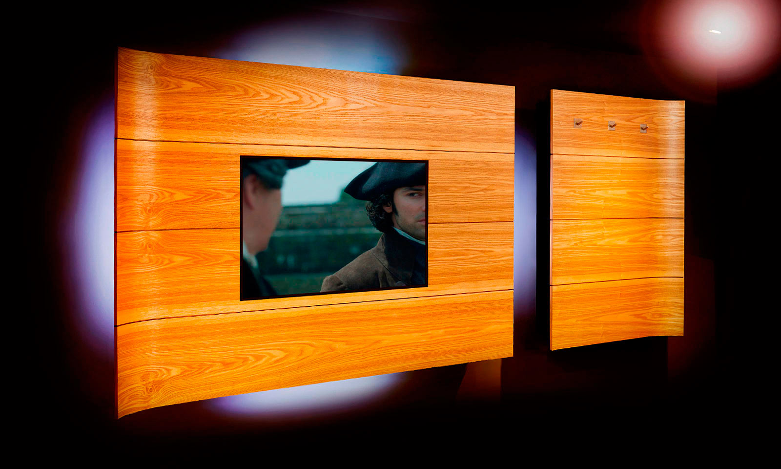 A bespoke, handmade, wall mounted home media centre, complete with hidden black shelving and LED lighting. Manufactured from curved Ash veneer, designed and installed by Mounts Hill Woodcraft.