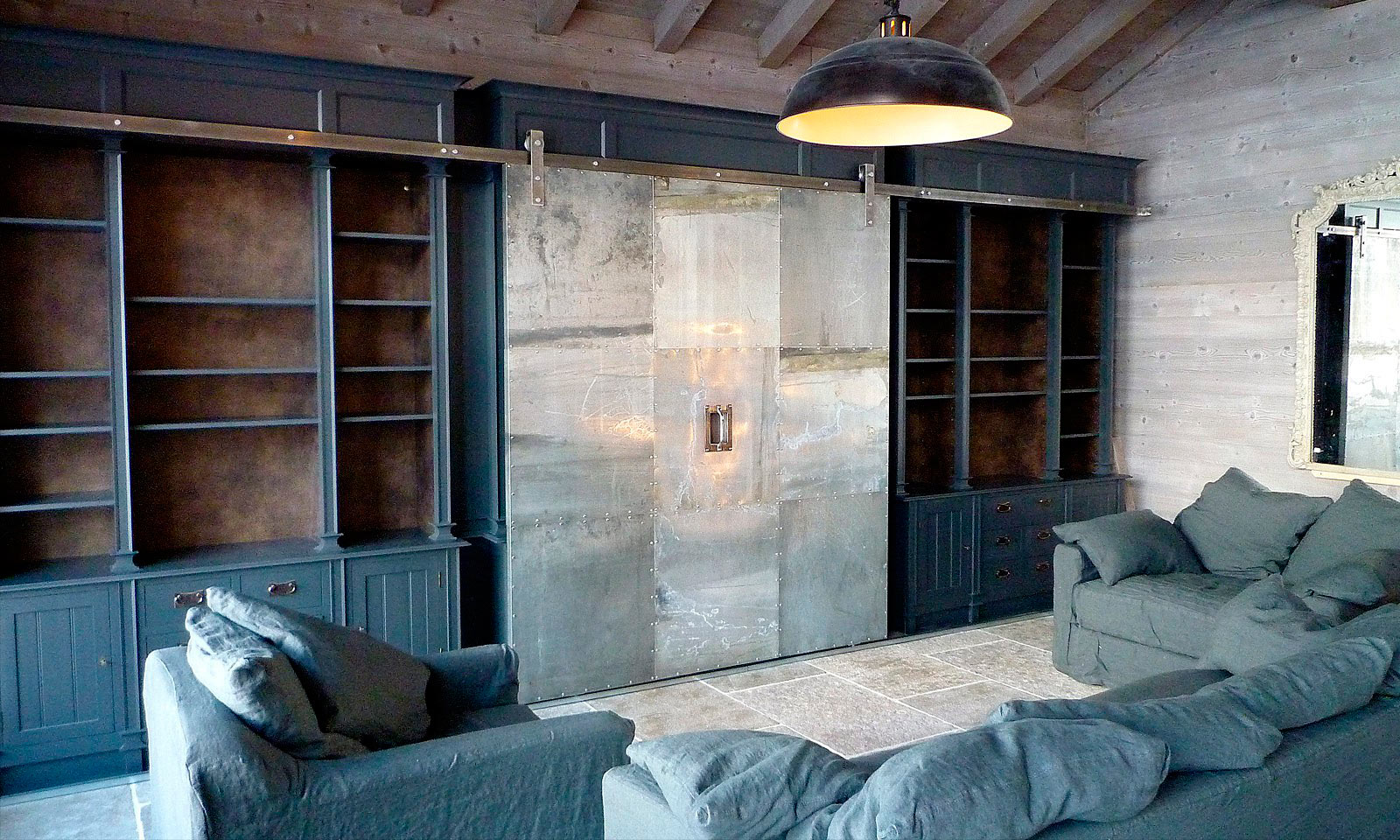 St Foy Media Unit. A bespoke and truly unique, full height media centre with an industrial twist. Manufactured for a ski chalet in St Foy, the unit features a riveted zinc sliding door and was hand-painted and installed by the skilled cabinet makers at Mounts Hill Woodcraft.
