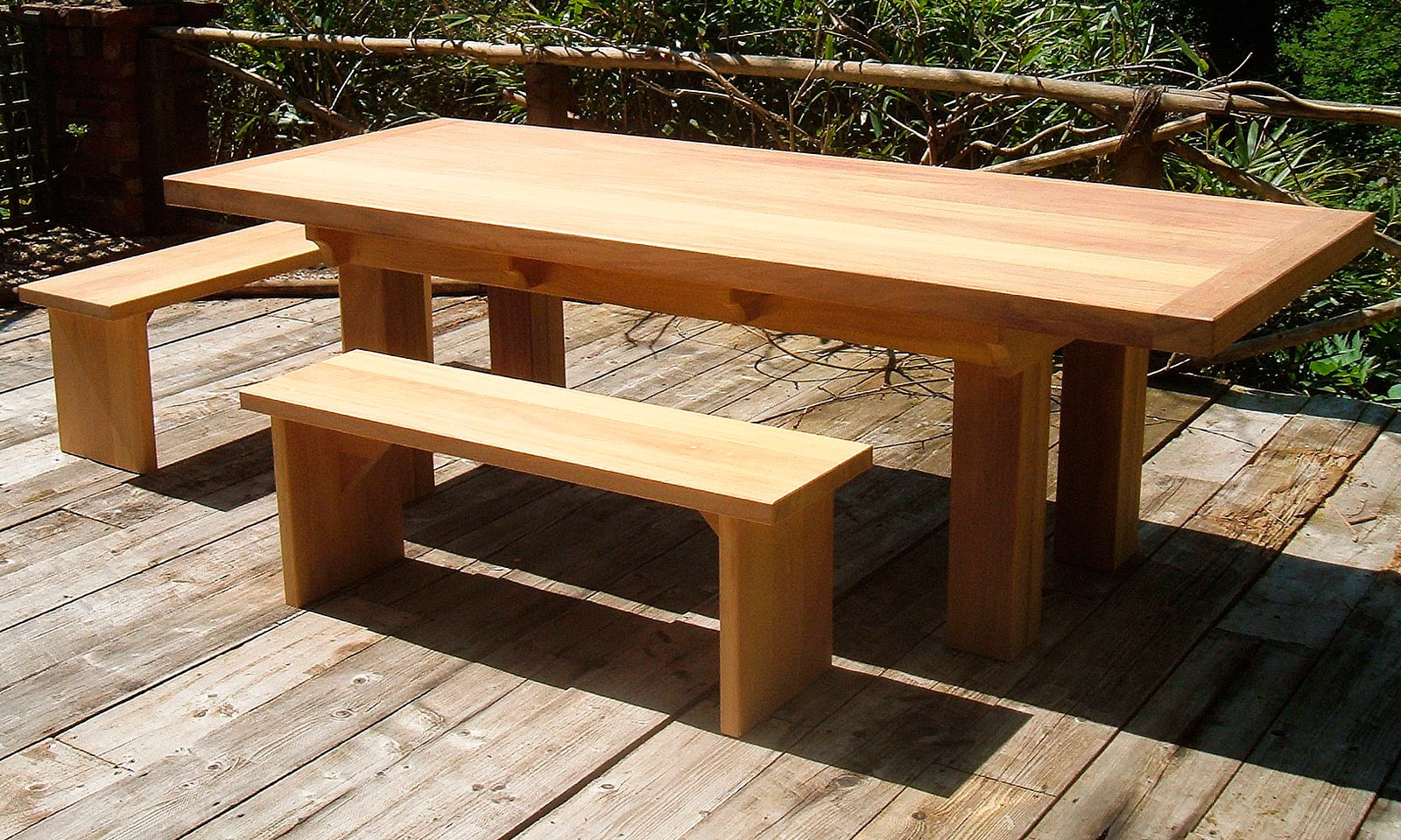 Iroko Table, with matching bench seats. A bespoke, handmade garden table manufactured out of Iroko hardwood. Quality hand-crafted exterior furniture designed and built by Mounts Hill.