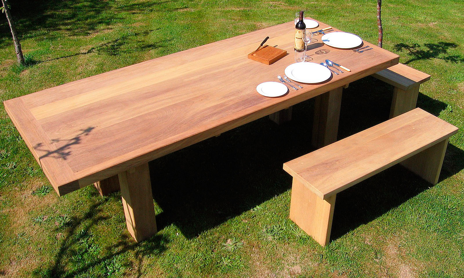 Iroko Table, with two matching bench seats. A bespoke, handmade garden table manufactured out of Iroko hardwood. Quality hand-crafted exterior furniture designed and built by Mounts Hill.