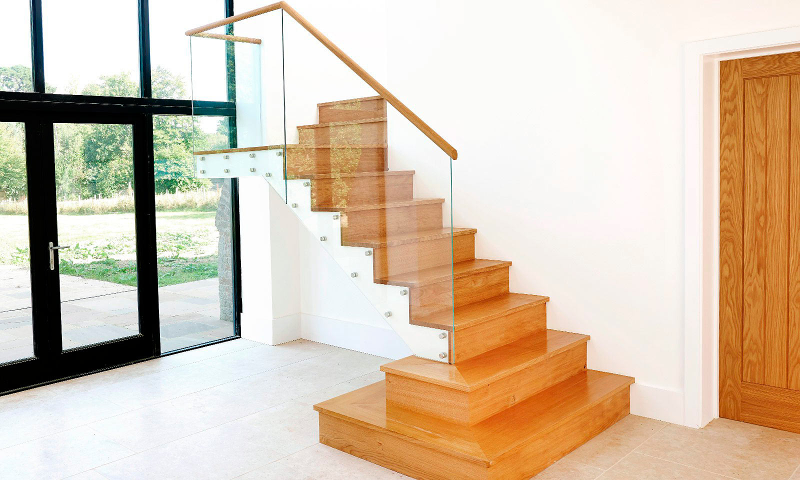 Modern Staircase. A contemporary oak staircase with a toughened glass bannister, manufactured from European oak and installed in this converted residential barn. Bespoke custom made joinery by Mounts Hill.